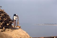 Woman winnowing grain by river